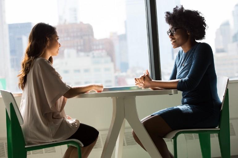 Две девушки беседуют за столиком у окна офисного здания.