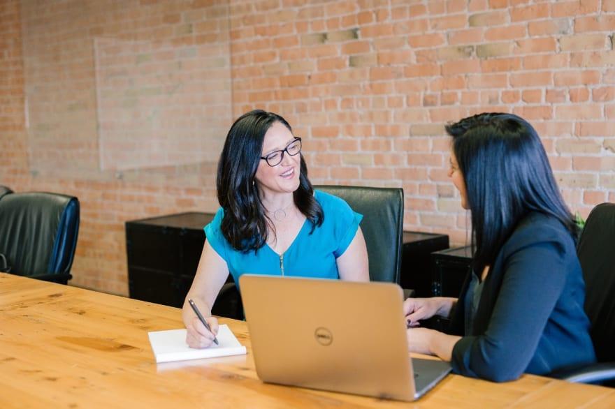 Две женщины за рабочим столом, на столе ноутбук. Одна объясняет что-то, вторая записывает в блокнот.