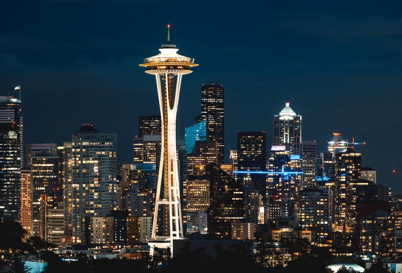 Светящаяся башня на фоне более темных высотных зданий ночью.