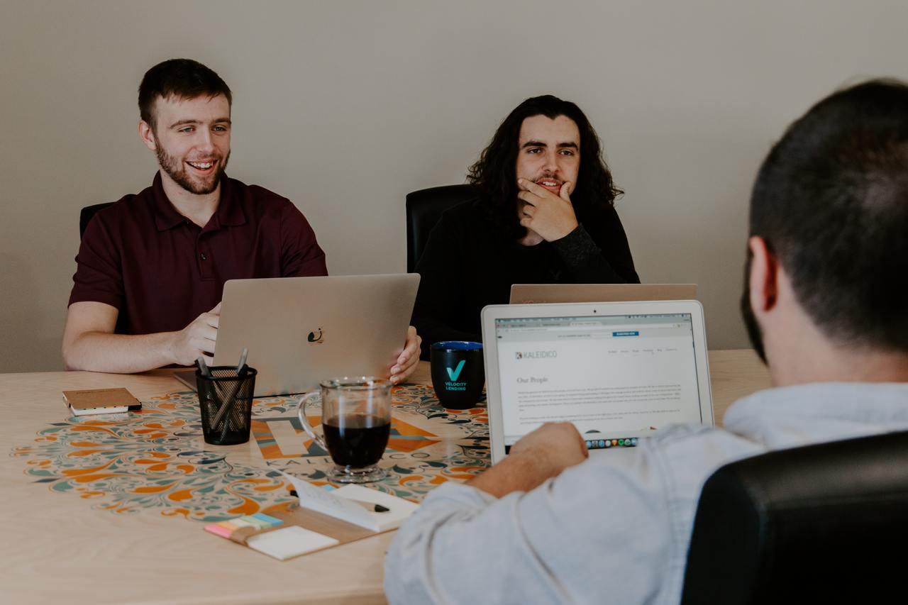 Трое парней с ноутбуками сидят и общаются за рабочим столом.