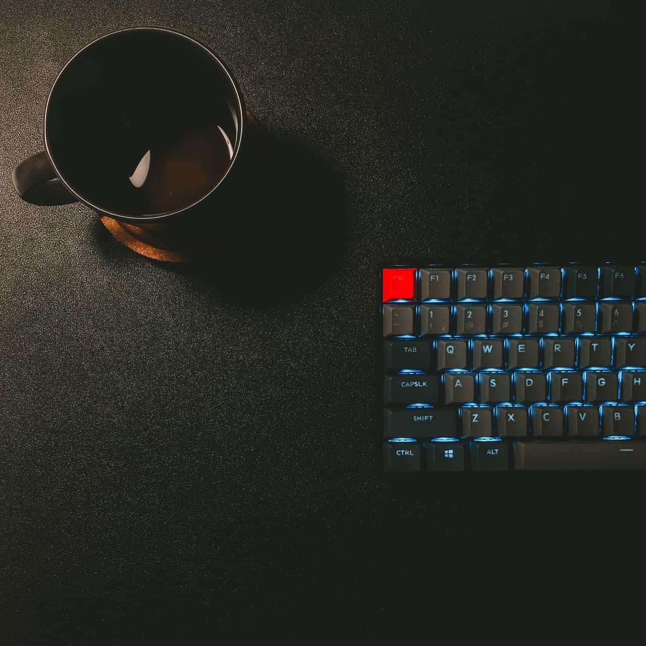 Рядом с клавиатурой стоит чашка чая