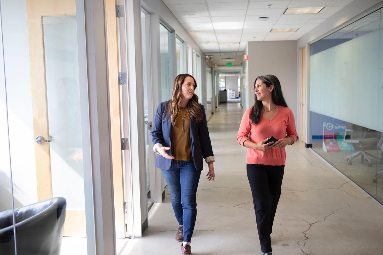 Две женщины идут по коридору офисного здания.