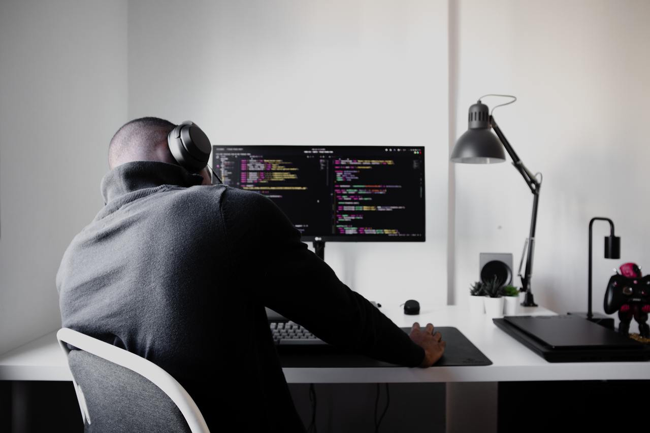 Программист в наушниках изучает код на экране.