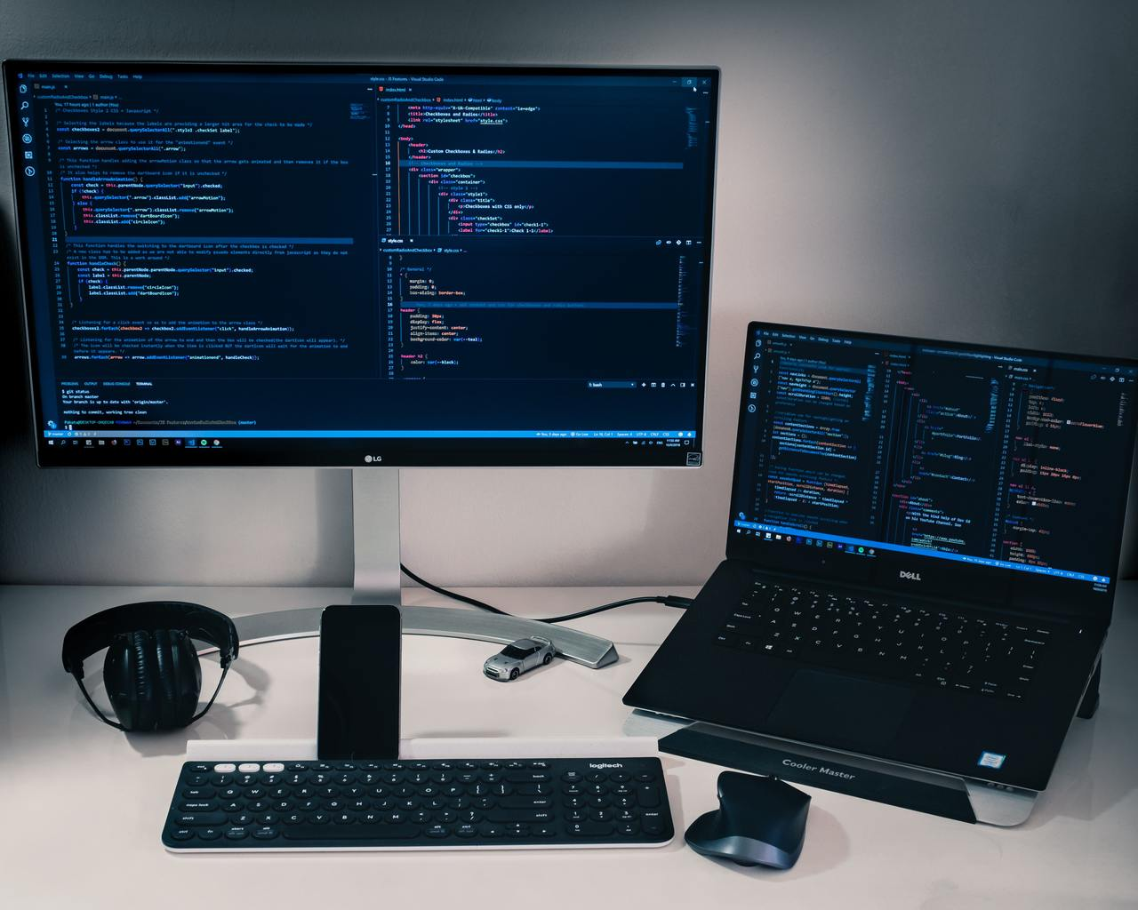 Рабочее место разработчика: монитор, клавиатура, мышь, наушники и ноутбук. На экранах - код.