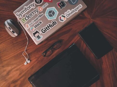 На столе лежат: закрытые ноутбук со множеством наклеек, мышь, наушники, телефон.