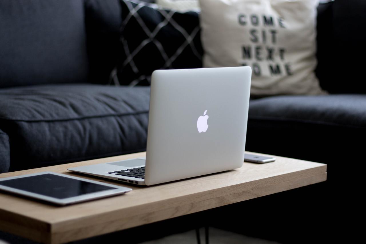 Ноутбук, планшет и смартфон на столике у дивана
