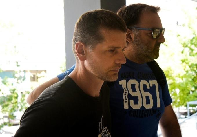 Полицейский в гражданском сопровождает предполагаемого сооснователя BTC-E Александра Винника в суд города Салоники. Фото Reuters